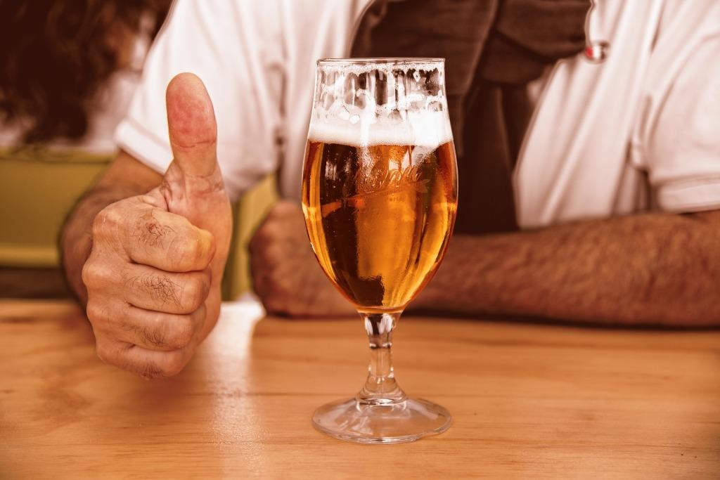 homme montrant son approbation devant un verre de bière.